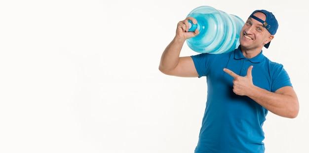 Repartidor feliz apuntando a la botella de agua y sonriendo