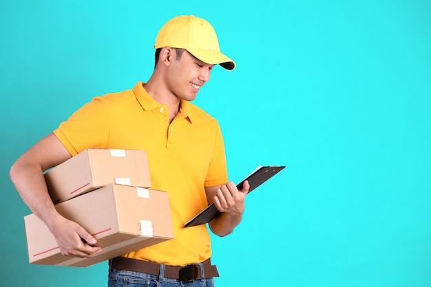 Repartidor feliz en camisa polo amarilla uniforme con paquete postal y lista de verificación