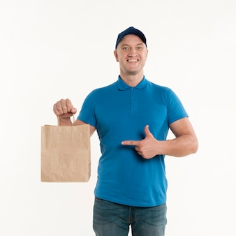 Repartidor feliz sosteniendo y apuntando a la bolsa de papel