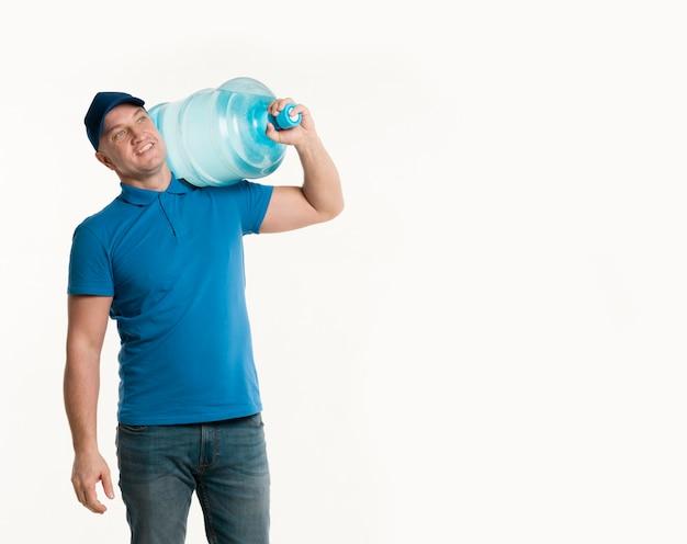 Repartidor feliz sosteniendo la botella de agua en el hombro con espacio de copia