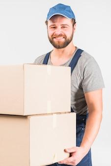 Repartidor feliz sosteniendo cajas grandes