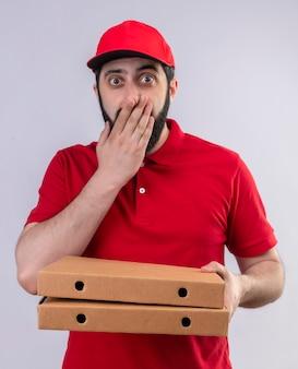 Repartidor guapo joven sorprendido vestido con uniforme rojo y gorra sosteniendo cajas de pizza y poniendo la mano en la boca aislada en la pared blanca