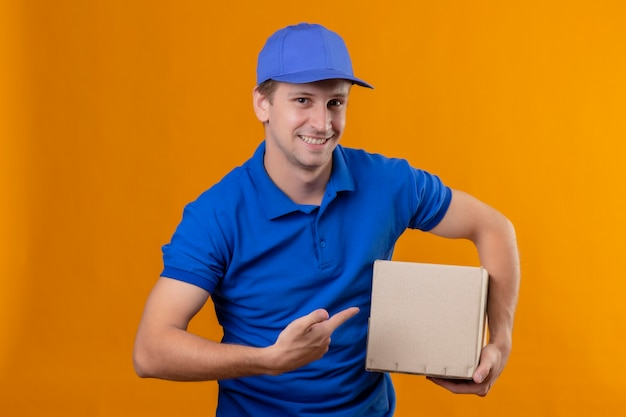 Repartidor guapo joven en uniforme azul y gorra con paquete de caja apuntando con el dedo a él