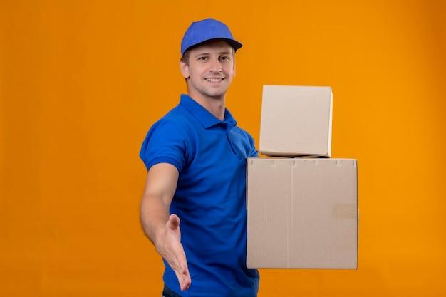 Repartidor guapo joven en uniforme azul y gorra sosteniendo cajas de cartón sonriendo saludo amistoso ofreciendo mano de pie sobre la pared naranja