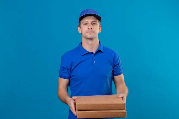 Repartidor guapo joven en uniforme azul y gorra sosteniendo cajas de pizza con expresión de confianza en la cara de pie sobre la pared azul
