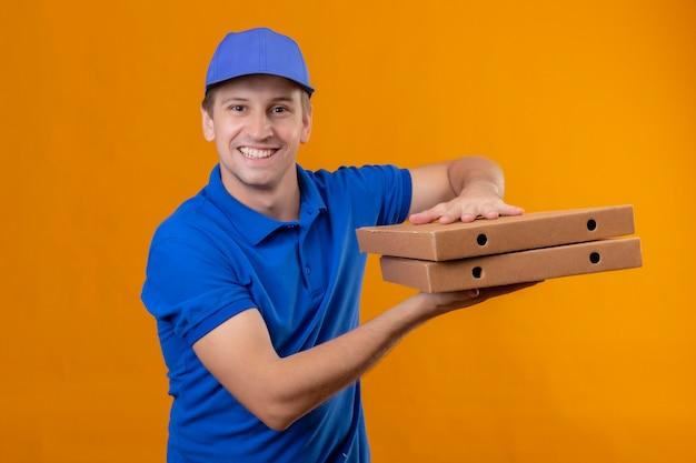 Repartidor guapo joven en uniforme azul y gorra sosteniendo cajas de pizza sonriendo amistoso de pie sobre la pared naranja