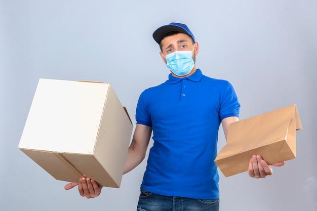 Repartidor joven con camisa polo azul y gorra en máscara médica protectora de pie con caja y paquete que tiene dudas con expresión de la cara confusa sobre fondo blanco aislado