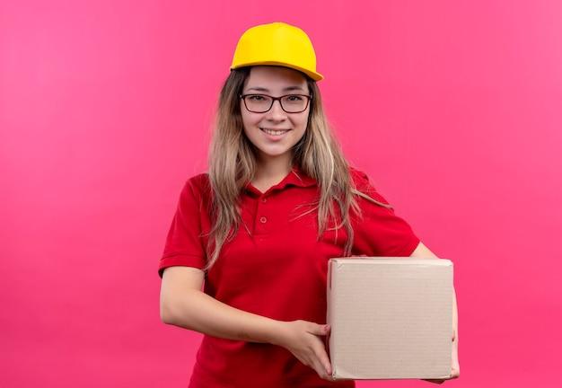 Repartidor joven en camisa polo roja y gorra amarilla con paquete de caja mirando a la cámara sonriendo confiado