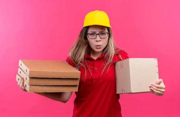 Repartidor joven en camisa polo roja y gorra amarilla con pila de cajas de pizza y paquete de caja mirando cametra con el ceño fruncido