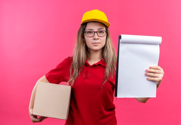Repartidor joven en camisa polo roja y gorra amarilla sosteniendo cajas de cartón que muestran el portapapeles con páginas en blanco pidiendo signatario que parece seguro