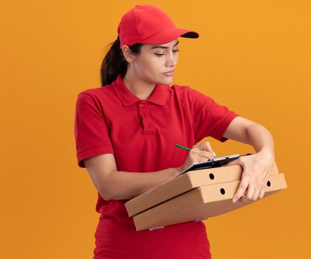 Repartidor joven confidente con uniforme y gorra escribiendo algo en el portapapeles en cajas de pizza aisladas en la pared naranja