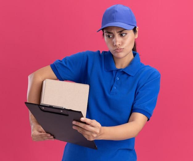 Repartidor joven confundido vistiendo uniforme con gorra sosteniendo la caja y mirando el portapapeles en su mano aislada en la pared rosa