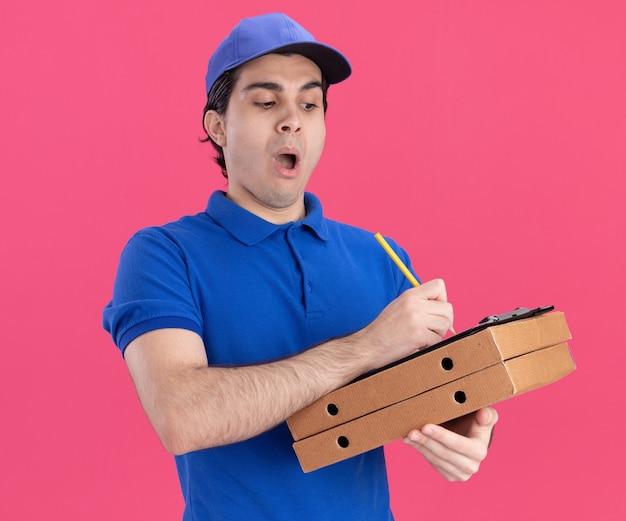 Repartidor joven impresionado con uniforme azul y gorra sosteniendo paquetes de pizza y portapapeles sobre ellos escribiendo en el portapapeles con lápiz aislado en la pared rosa