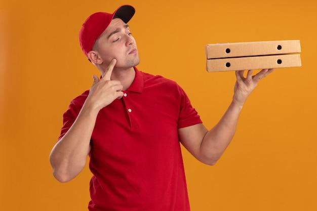 Repartidor joven impresionado con uniforme con gorra sosteniendo y mirando cajas de pizza poniendo el dedo en la mejilla aislado en la pared naranja