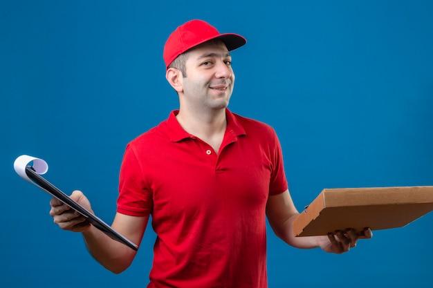 Repartidor joven en polo rojo y gorra de pie con caja de pizza y portapapeles en manos sonriendo amigable con cara feliz sobre fondo azul aislado