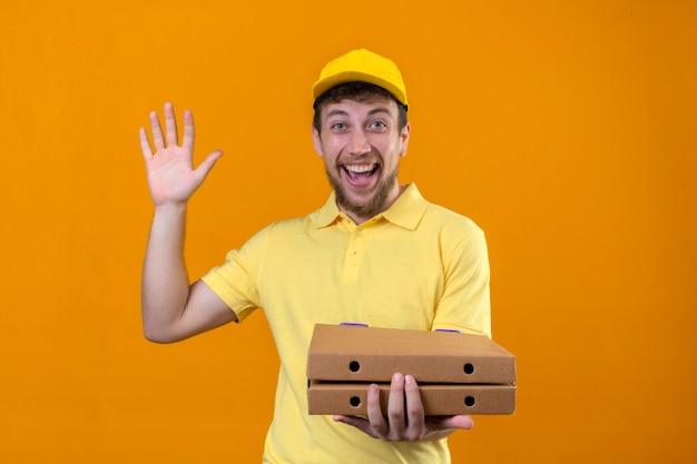 Repartidor joven positivo en camisa polo amarilla y gorra sosteniendo cajas de pizza mirando alegre haciendo gesto de bienvenida saludando con la mano en naranja aislado