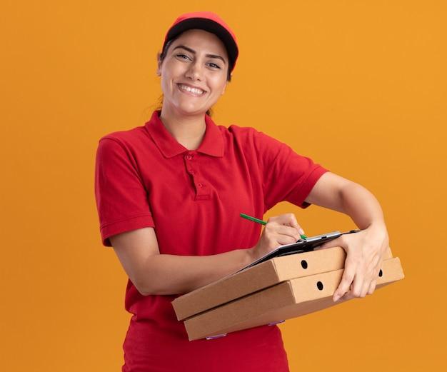Repartidor joven sonriente mirando al frente vistiendo uniforme y gorra escribiendo algo en el portapapeles en cajas de pizza aisladas en la pared naranja
