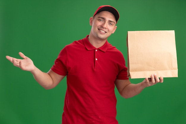 Repartidor joven sonriente con uniforme y gorra sosteniendo el paquete de alimentos de papel y extendiendo la mano aislada en la pared verde