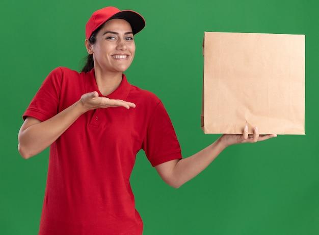 Repartidor joven sonriente con uniforme y gorra sosteniendo y puntos en el paquete de alimentos de papel aislado en la pared verde