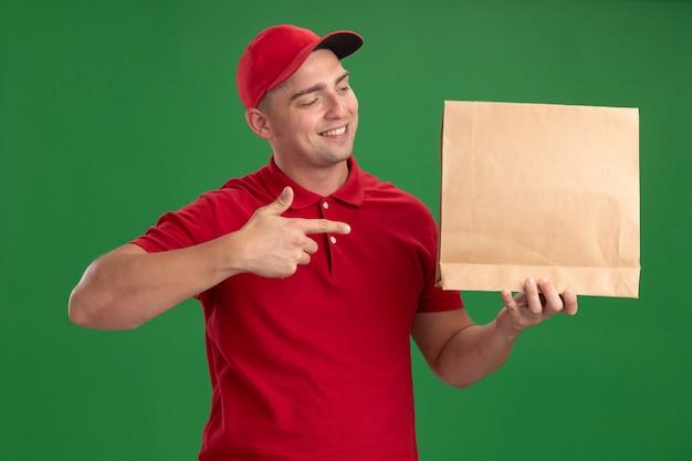 Repartidor joven sonriente con uniforme y gorra sosteniendo y puntos paquete de comida de papel aislado en la pared verde
