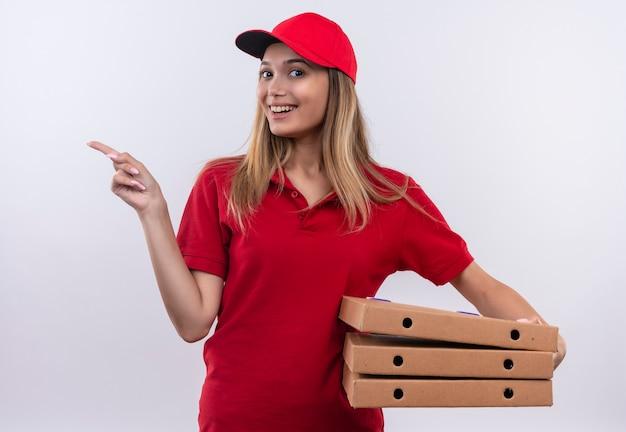 Repartidor joven sonriente con uniforme rojo y gorra sosteniendo la caja de pizza y apunta al lado aislado en la pared blanca