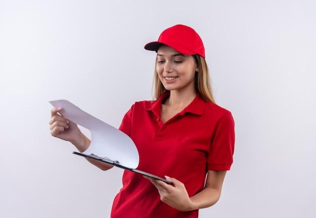 Repartidor joven sonriente con uniforme rojo y gorra sosteniendo y hojeando a través del portapapeles aislado en blanco
