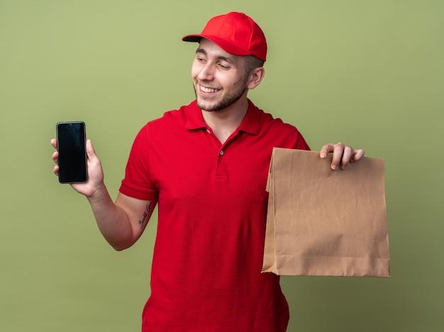 Repartidor joven sonriente vistiendo uniforme con gorra sosteniendo una bolsa de comida de papel mirando el teléfono en la mano