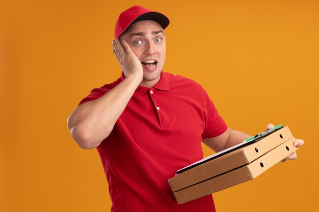 Repartidor joven sorprendido vestido con uniforme con gorra sosteniendo cajas de pizza con portapapeles poniendo la mano en la mejilla aislada en la pared naranja