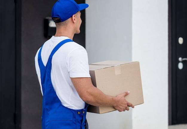 Repartidor joven sostiene una caja de cartón en sus manos