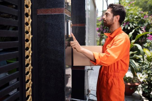 Repartidor joven tocando la campana para la entrega de la caja