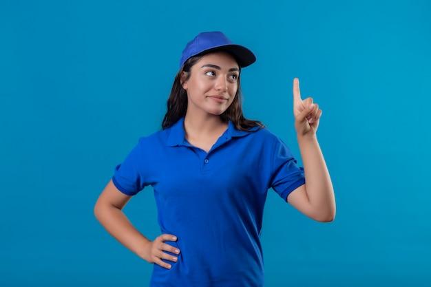 Repartidor joven en uniforme azul y gorra apuntando con el dedo hacia arriba pensando en positivo con sonrisa de confianza en la cara de pie sobre fondo azul.