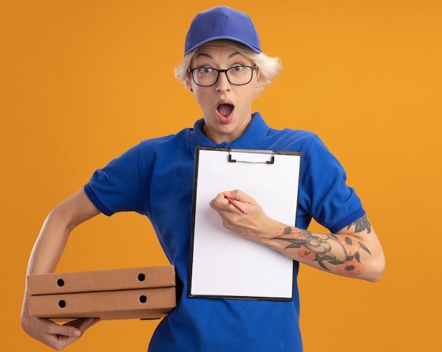 Repartidor joven en uniforme azul y gorra con gafas sosteniendo cajas de pizza y portapapeles con páginas en blanco y lápiz mirando asombrado y sorprendido sobre la pared naranja