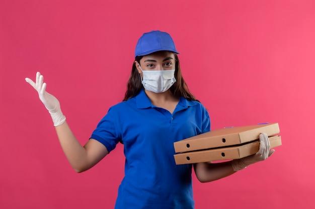 Repartidor joven en uniforme azul y gorra con máscara protectora facial y guantes sosteniendo cajas de pizza mirando a la cámara sonriendo seguro positivo y feliz de pie sobre fondo rosa
