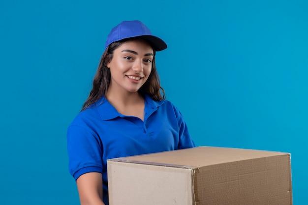 Repartidor joven en uniforme azul y gorra con paquete de caja mirando a la cámara sonriendo confiada feliz y positiva de pie sobre fondo azul.