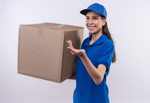 Repartidor joven en uniforme azul y gorra sosteniendo una caja de cartón grande sonriendo alegremente