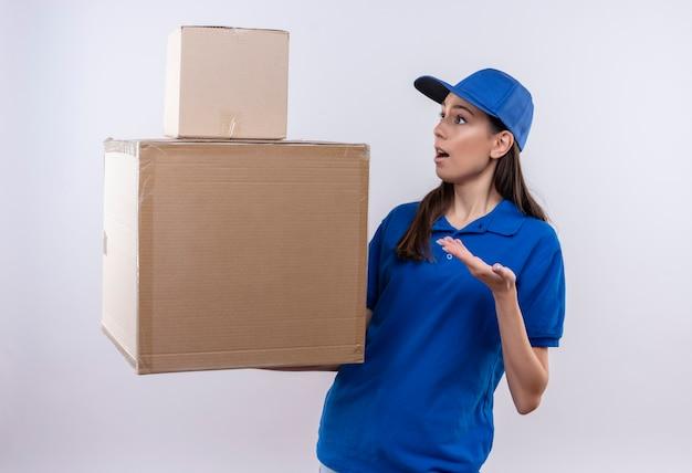 Repartidor joven en uniforme azul y gorra sosteniendo cajas de cartón con aspecto confundido y sorprendido