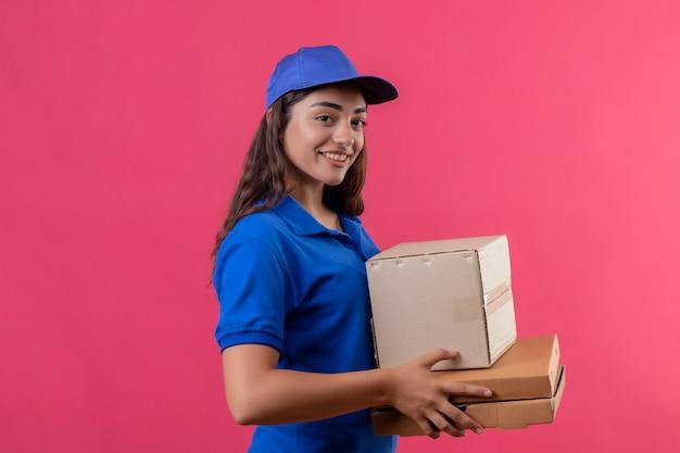 Repartidor joven en uniforme azul y gorra sosteniendo cajas de cartón mirando a la cámara sonriendo confiada feliz y positiva de pie sobre fondo rosa