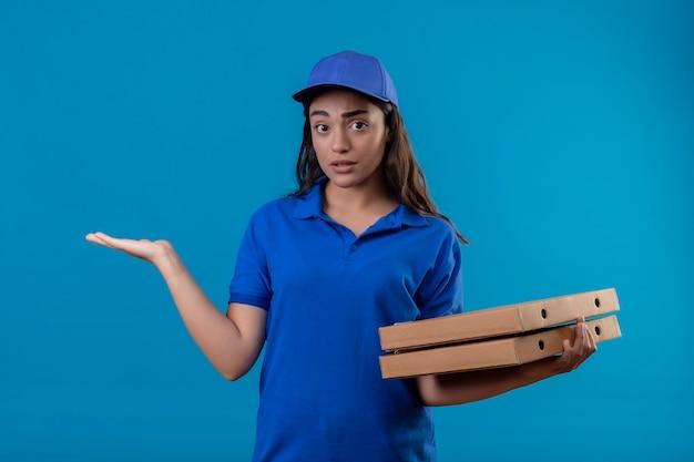 Repartidor joven en uniforme azul y gorra sosteniendo cajas de pizza despistado y confundido de pie con el brazo levantado sin respuesta sobre fondo azul.