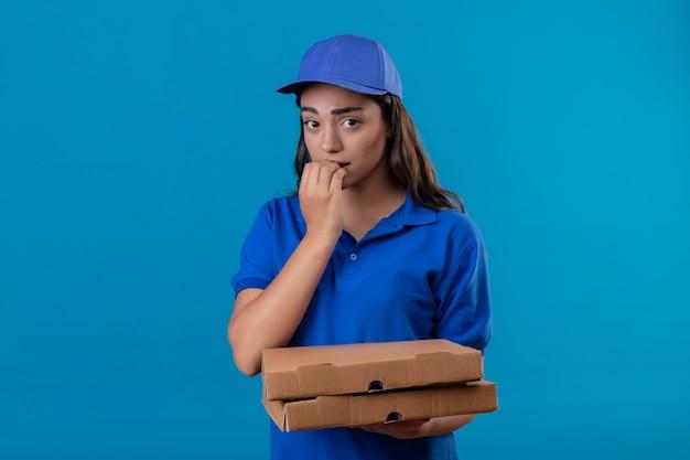 Repartidor joven en uniforme azul y gorra sosteniendo cajas de pizza mirando a la cámara nervioso y estresado morderse las uñas de pie sobre fondo azul