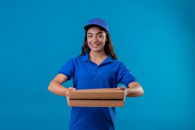 Repartidor joven en uniforme azul y gorra sosteniendo cajas de pizza mirando a la cámara sonriendo confiada feliz y positiva de pie sobre fondo azul.