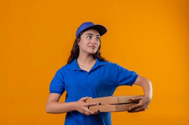 Repartidor joven en uniforme azul y gorra sosteniendo cajas de pizza mirando a un lado con sonrisa de confianza en la cara de pie sobre fondo amarillo