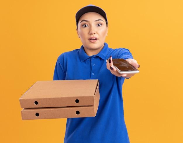 Repartidor joven en uniforme azul y gorra sosteniendo cajas de pizza mostrando smartphone mirando al frente siendo sorprendido y confundido de pie sobre la pared naranja