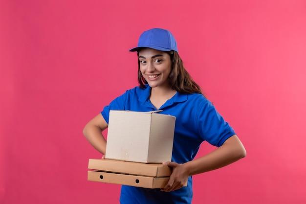 Repartidor joven en uniforme azul y gorra sosteniendo cajas de pizza y paquete de caja mirando a la cámara sonriendo alegremente feliz y positivo de pie sobre fondo rosa
