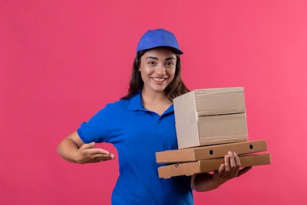 Repartidor joven en uniforme azul y gorra sosteniendo cajas de pizza y paquete de caja que presenta con el brazo de la mano sonriendo alegremente feliz y positivo de pie sobre fondo rosa