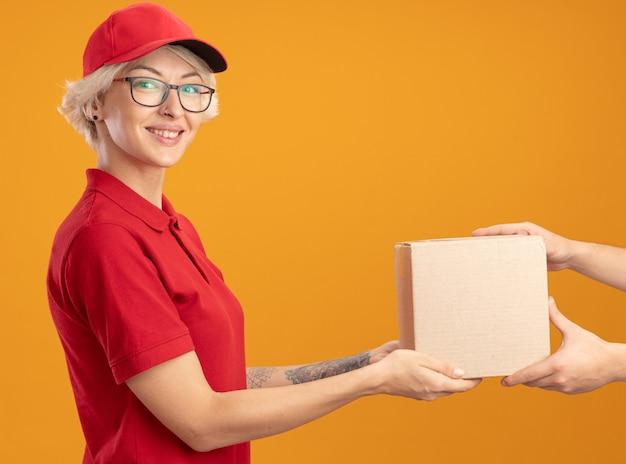 Repartidor joven en uniforme rojo y gorra con gafas dando caja de cartón a u cliente sonriendo amistoso de pie sobre la pared naranja