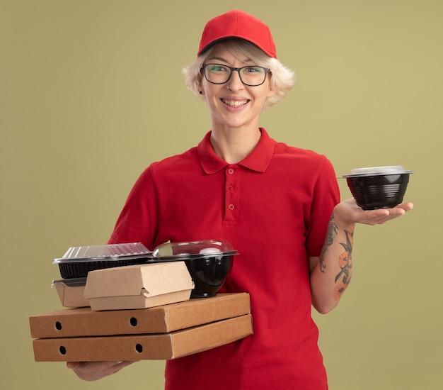 Repartidor joven en uniforme rojo y gorra con gafas sosteniendo cajas de pizza y paquetes de alimentos sonriendo con cara feliz de pie sobre la pared verde