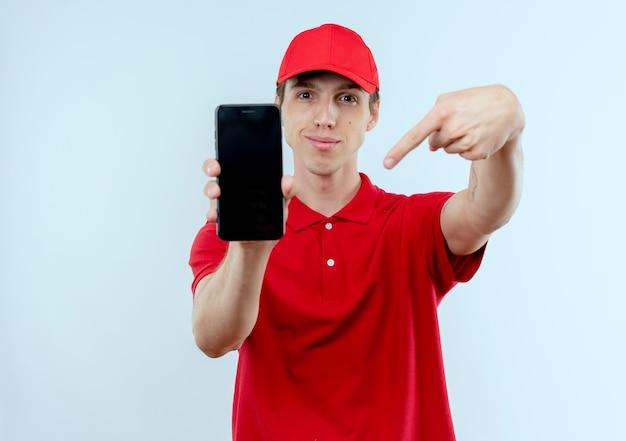 Repartidor joven en uniforme rojo y gorra mostrando smartphone apuntando con el dedo hacia él mirando confiado de pie sobre la pared blanca