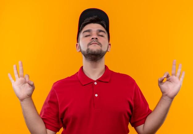 Repartidor joven en uniforme rojo y gorra relajante con los ojos cerrados haciendo gesto de meditación con los dedos