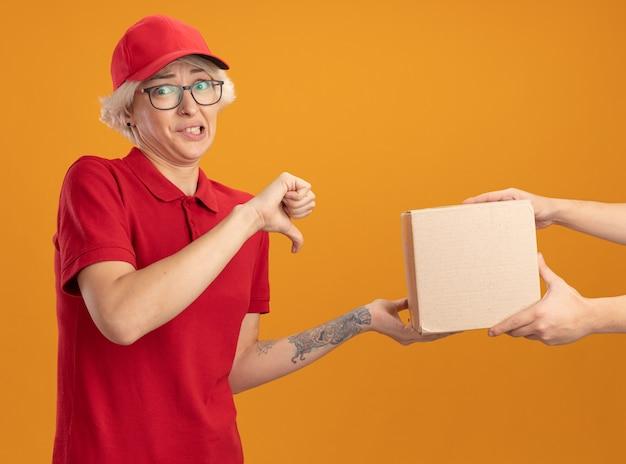 Repartidor joven en uniforme rojo y gorra sintiéndose disgustado mientras recibe el paquete de caja mostrando los pulgares hacia abajo de pie sobre la pared naranja