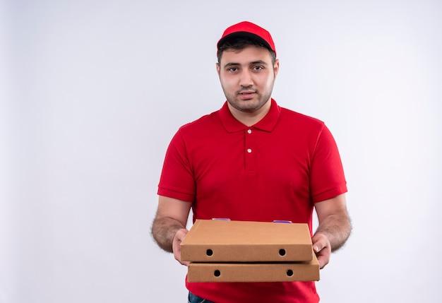 Repartidor joven en uniforme rojo y gorra sosteniendo cajas de pizza sonriendo confiado de pie sobre la pared blanca